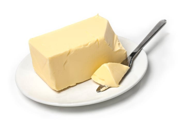 Piece of butter on white plate with knife. White background and shallow focus.